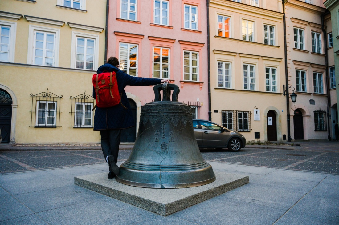 Girl with red backpack at the wishing bell in Warsaw